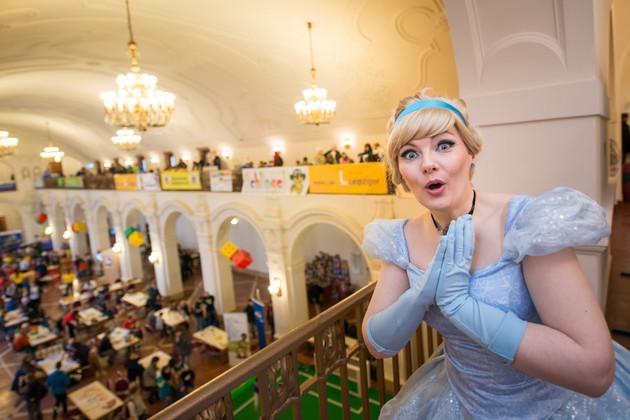Im rechten Bildvordergrund sieht man eine Prinzessin in einem blauen Kleid, welche über die Spieleangebote staunt. Sie steht auf der Empore mit Blick auf die Spieltische in der Oberen Wandelhalle.