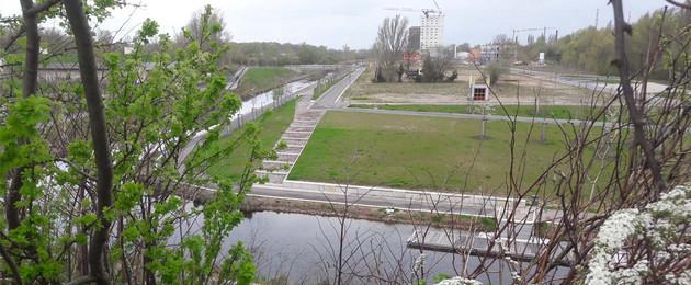 Blick über die neue Promenade und Freiflächen am Lindenauer Hafen im Hintergrund sind Baukräne zu sehen