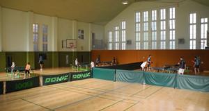Sporthalle Breitschuhstraße in der mehrere Kinder und Jugendliche Tischtennis an mehreren Tischen spielen.