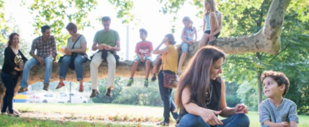 Junge Menschen unterschiedlicher Herkunft sitzen auf einem Baumstamm, zwei davor auf einer Wiese