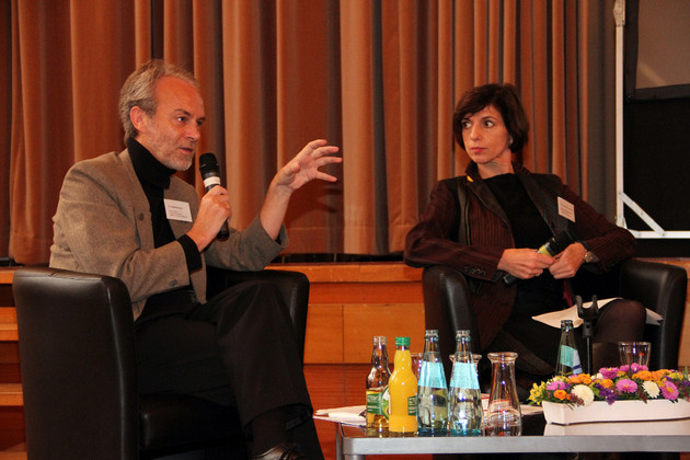 Ein Herr in Jacket und Rollkragenpullover im Gespräch mit einer interessiert zuhörenden Dame während einer Podiumsdiskussion.