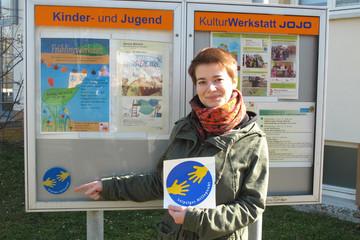 Bild wird vergrößert: Eine Frau steht vor eine Schautafel und hält einen Aufkleber in der Hand mit dem Logo des Leipziger Hilfepunkts.