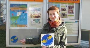 Eine Frau steht vor eine Schautafel und hält einen Aufkleber in der Hand mit dem Logo des Leipziger Hilfepunkts.