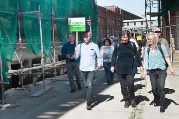 """Bild wird vergrößert: Eine Gruppe Menschen läuft an einem im bau befindlichen Haus vorbei. Ein Mann hält ein Schild mit der Aufschrift """"Führung"""" in der Hand."""