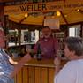 Blick in hölzernen Verkaufsstand. Winzer hinter, zwei Gäste mit gefüllten Weingläsern vor dem Tresen.