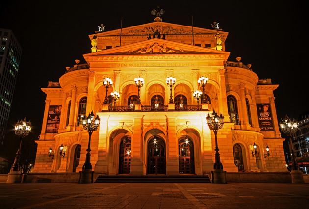 """Frontansicht der Alten Oper mit drei großen Eingangsbögen und einer Terasse darüber. Am Giebel steht geschrieben """"Dem Wahren Schönen Guten""""."""