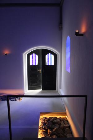 Ein blau beleuchteter Raum mit Blick zu einer schwarzen Tür
