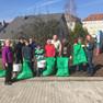 Gruppe von Menschen steht zusammen mit gefüllten Müllsäcken und Eimern voll gesammelten Müll.