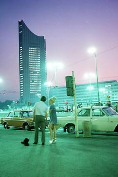 Bild wird vergrößert: Das City-Hochhaus 1973 in der Abenddämmerung. Zwei Menschen stehen neben der Straße an der zwei Autos geparkt sind.