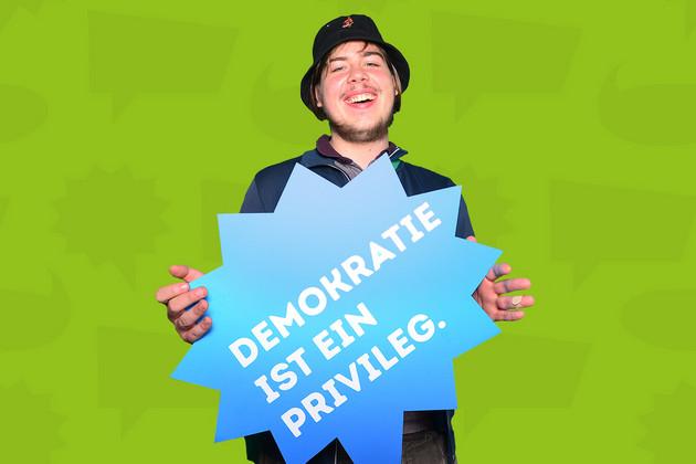 Junger Mann zur Statementkampagne zum Jahr der Demokratie mit blauer Sprechblase auf der steht: Demokratie ist ein Privileg.