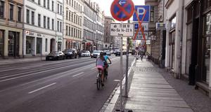 Straße mit Radfahrern und Verkehrsschildern Halteverbot und Parken durchgestrichen.