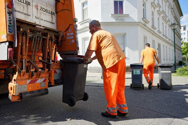 Ein Mitarbeiter der Stadtreinigung hängt eine Mülltonne zur Entleerung an ein Müllauto. Ein weitere Mitarbeiter bringt zwei Mülltonnen zum Abstellplatz.