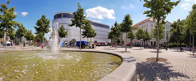 """Brunnen mit Wasserfontäne vor der mit Blech verkleideten, runden Fassade des ehemaligen Kaufhauses """"Blechbüchse"""""""