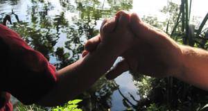 Die Hand eines Erwachsenen umschließt die Hand eines Kindes