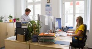 Ein junger Mann steht vor seinem Schreibtisch, am Schreibtisch ihm gegenüber sitzt eine junge Frau.