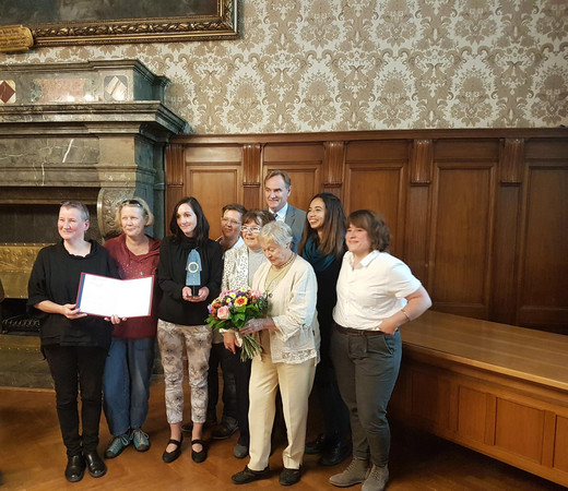 Acht Frauen der Frauenkultur Leipzig und der Oberbürgermeister stehen in einer kleinen Gruppe zusammen und halten in den Händen die Urkunde, den Preisgegenstand und einen Blumenstrauß.
