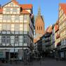 Einblick in eine Gasse mit Fachwerkhäusern und Blick auf eine Kirche mit roten Backsteinen