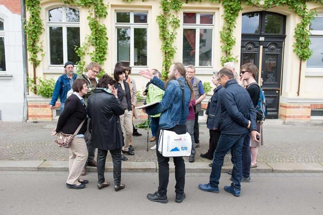Eine Menschengruppe steht bei einer Führung beisammen. Hinter der Gruppe ist ein Haus, dessen Wände zum Teil mit Kletterpflanzen bewachsen ist.