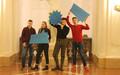 Vier Jugendliche stehen nebeneinander und halten Sprechblasenschilder hoch: Democracy, We are all in this und Together.