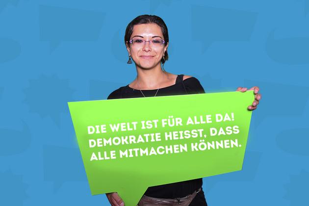 """Eine Frau hält eine Schild mit dem Statement """"Die Welt ist für alle da! Demokratie heisst, dass alle mitmachen können.""""."""