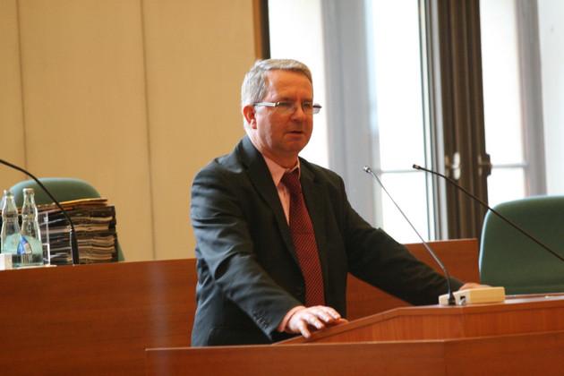 Prof. Dr. Thomas Hofsass steht hinter einem Rednerpult und spricht.