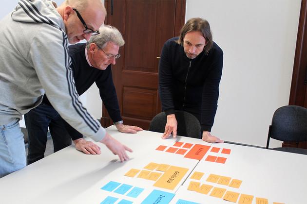 Drei Menschen sind über einen Tisch, auf dem bunte Karten liegen, gebeugt und wählen die Teilnehmer des Forums aus.