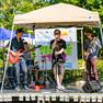 vier männliche Jugendliche mit Instrumenten auf einer Bühne