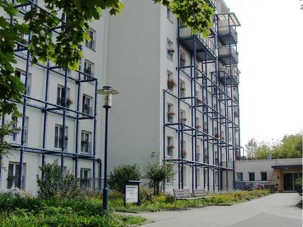 Blick auf ein großes graues Haus mit blauen Stangen außen. Davor ein Schild: Deutsches Rotes Kreuz