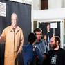 Drei Menschen unterhalten sich vor einem Plakatbanner, auf dem eine ältere Frau zu sehen ist