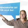 """Die Stadträtin Nicole Wolfahrt hält ein Schild mit dem Statement """"Demokratie ist für Alle da!""""."""