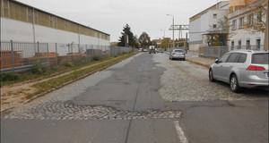 Schlechter Straßenzustand der Franz-Flemming-Straße. Die Straßenoberfläche besteht aus altem Natursteinpflaster, welches bereichsweise mit Asphalt geflickt ist. Der östliche Gehweg ist unbefestigt und teilweise mit Rasen bewachsen.