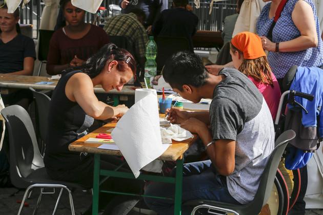 Drei junge Menschen malen an einem Basteltisch.