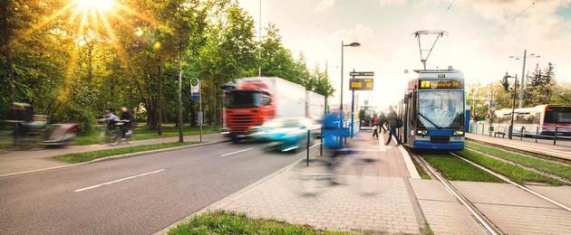 Straßensituation mit haltender Straßenbahn, Fahrradfahrern, LKW und Autoverkehr und Fußgängern. Die Sonne scheint tief über Bäume am Straßenrand.