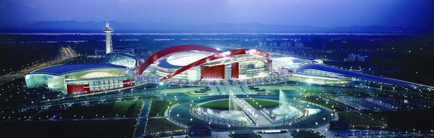 Ansicht des beleuchteten Nanjing Stadions am Abend: rote Dachbögen und auf dem Vorplatz Springbrunnen