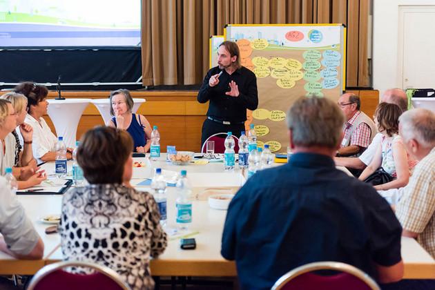 Eine Gruppe diskutiert am Tisch, der Moderator steht vorne an der Pinnwand