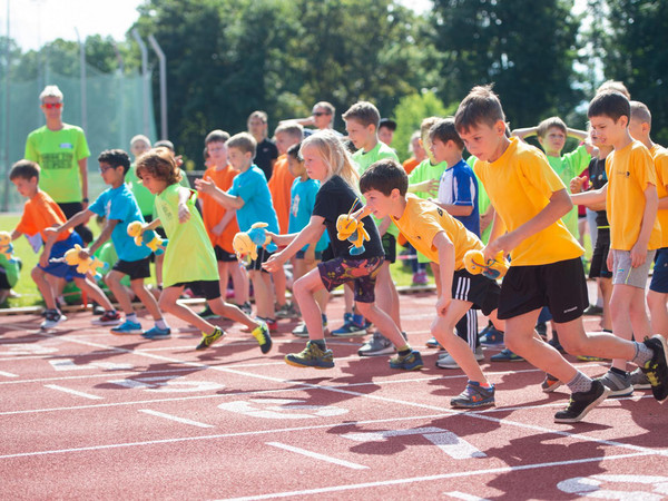 Kinder in orangenen T-Shirts bei einem Staffellauf im Sommer