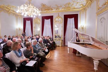 Bild wird vergrößert: Ein Saal mit üppigen Goldverzierungen und Stuck an Wänden und Decke. Eine Pianistin spielt vor Publikum an einem weißen Flügel.