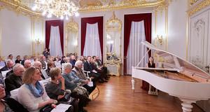Ein Saal mit üppigen Goldverzierungen und Stuck an Wänden und Decke. Eine Pianistin spielt vor Publikum an einem weißen Flügel.