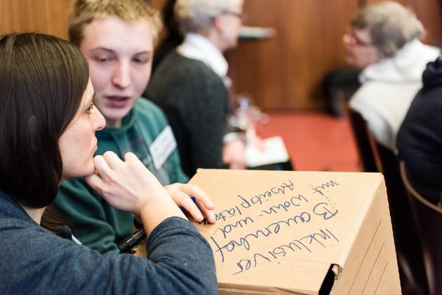 Eine junge Frau und ein junger Mann sind im Gespräch. Die Frau stützt den Arm auf einer handschriftlich beschriebenen Pappe ab und den Kopf auf ihrer Hand. Sie schaut nachdenklich. In der anderen Hand hält sie einen Stift.