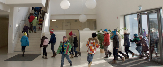 A group of kids is running through the entrance area of a school.