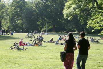 Bild wird vergrößert: Menschen liegen auf einer Wiese im Clara-Zetkin-Park