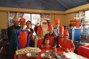 Bild wird vergrößert: Der Weihnachtsmann posiert mit Kindern und Helfern in der Wichtelwerkstatt