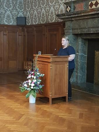 Eine Frau steht hinter dem Rednerpult und spricht zu den Gästen.