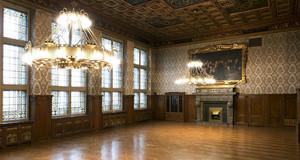 Blick in den leeren prachtvollen Ratsplenarsaal im Neuen Rathaus. Von der aufwendig gestalteten Decke hängen zwei Kronleuchter.