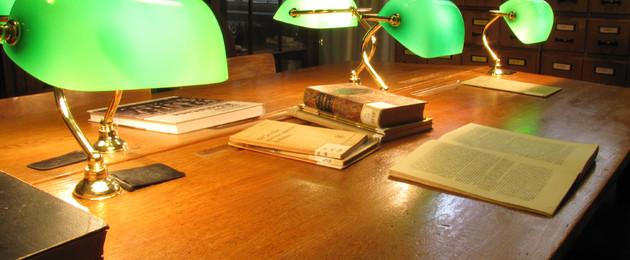 Die Lese- und Arbeitsplätze der Bibliothek der Leipziger Schulmuseums. Zwei gegeneinander gestellte Tische, vier Leselampen mit grünen Glasschirmen, zudem Literatur. .