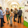 Blick in die Ausstellung. Viele Menschen stehen vor mannshohen Ausstellungstafeln und unterhalten sich.