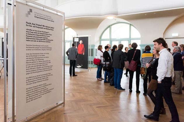Eine Gruppe von Menschen steht in der Kongresshalle und betrachtet eine Ausstellung.