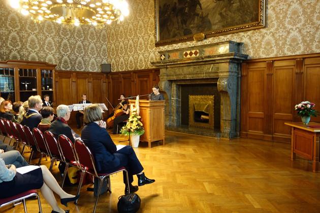 Festveranstaltung in einem festlichen Saal im Neuen Rathaus. Das Publikum sitz auf Stühlen und hört einer Sprecherin zu, die hinter einem Stehpult redet.