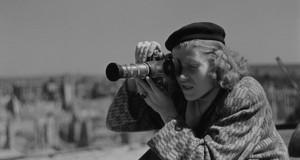 Schwarz-Weiß-Foto von Renate Rössing in Mantel und Baskenmütze mit Kamera in der Hand, konzentriert fotografierend.