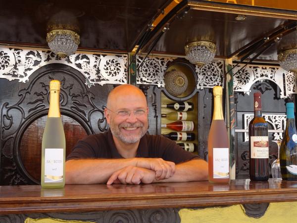 Mann lacht zwischen zwei Weinflaschen hindurch